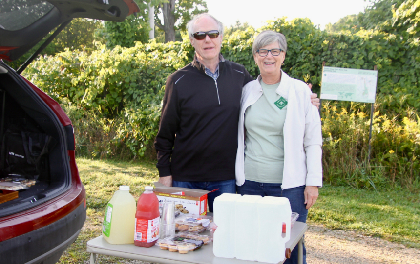 Bruce Trail volunteers ready at first hiker checkpoint of Falling Waters challenge with snacks and drinks. Hikers walk to shuttle bus to take them to trailhead at start of Beaver Valley Bruce Trail Club End-to-End hike