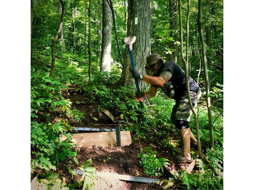 BVBTC volunteer pounds stake in ground to hold stair riser